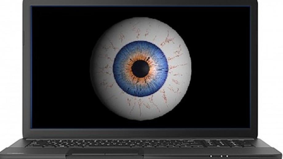 Photo of eyeball on screen of laptop