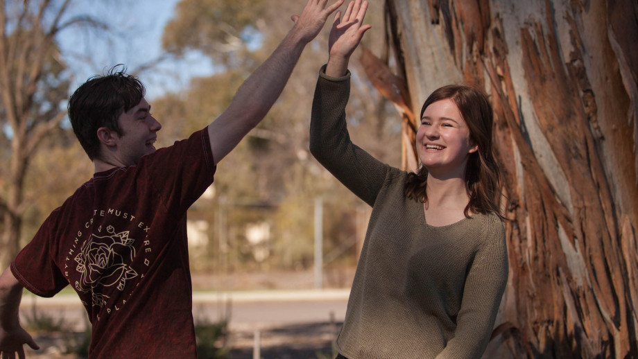 Seraina and Matt both students on rural scholarships hi-five and smile