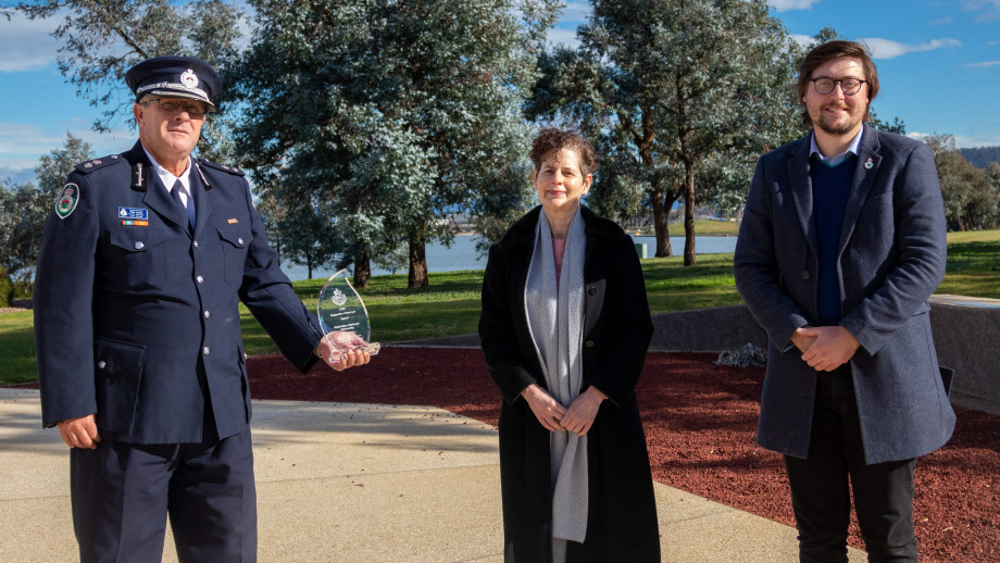 NSW RFS District Manager for Lake George Supt. Paul Jones presents the award to Professor Catherine Waldby and Russell Buzby.