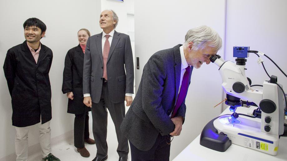 Professor Ian Mattaj, Director General of the European Molecular Biology Laboratory looks through a microscope with Australia's Chief Scientist Alan Finkel, during a tour of the John Curtin School of Medical Research, ANU