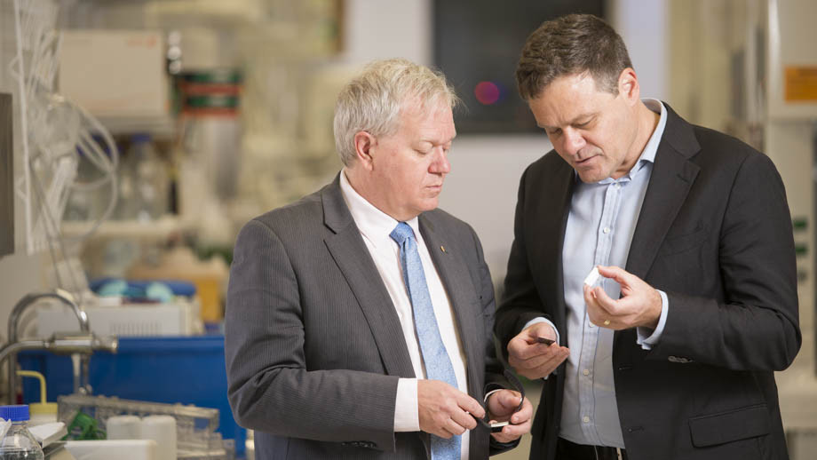 Professor Brian Schmidt and Professor Mark Kendall inspect a wearable device being developed by WearOptimo. Image credit: ANU