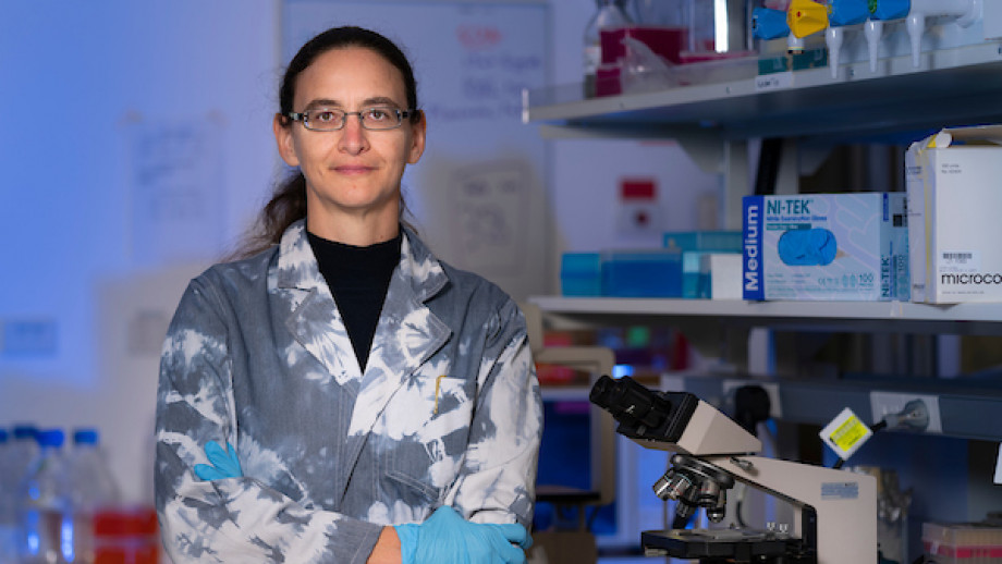 Associate Professor Aude Fahrer stands in a lab next to a microscrope, wearing a silver jacket.
