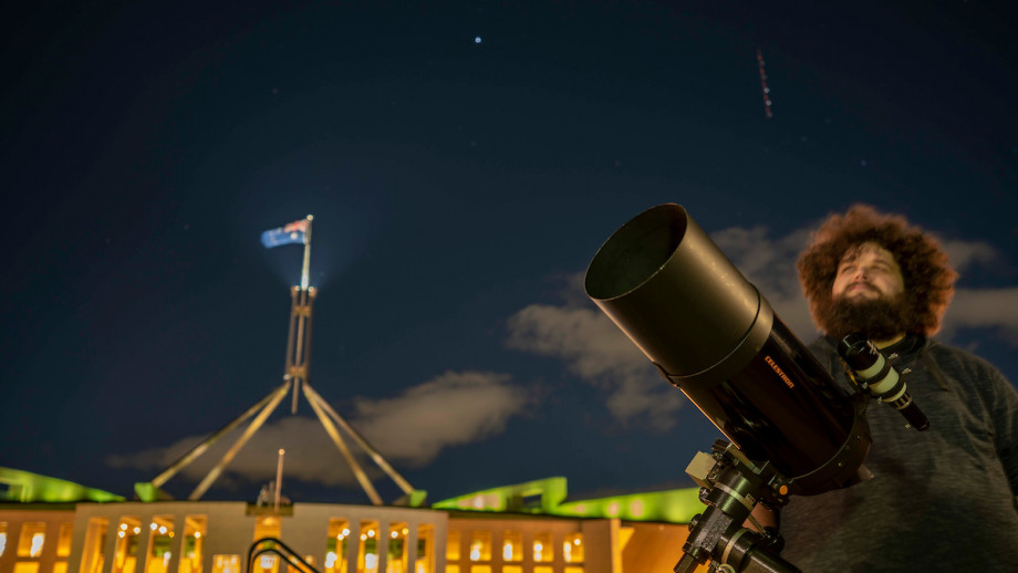 Pete Swanton with a shooting star in the background, during the stargazing event he ran for our community on the side of Parliament House. Credit: Jamie Kidston, ANU