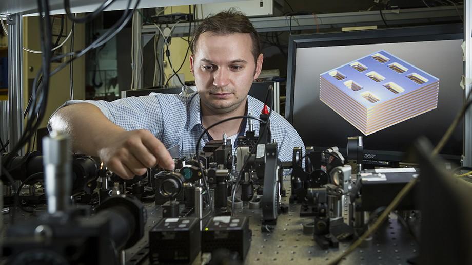 Dr Kruk next to a diagram of the metamaterial structure. Image Stuart Hay, ANU