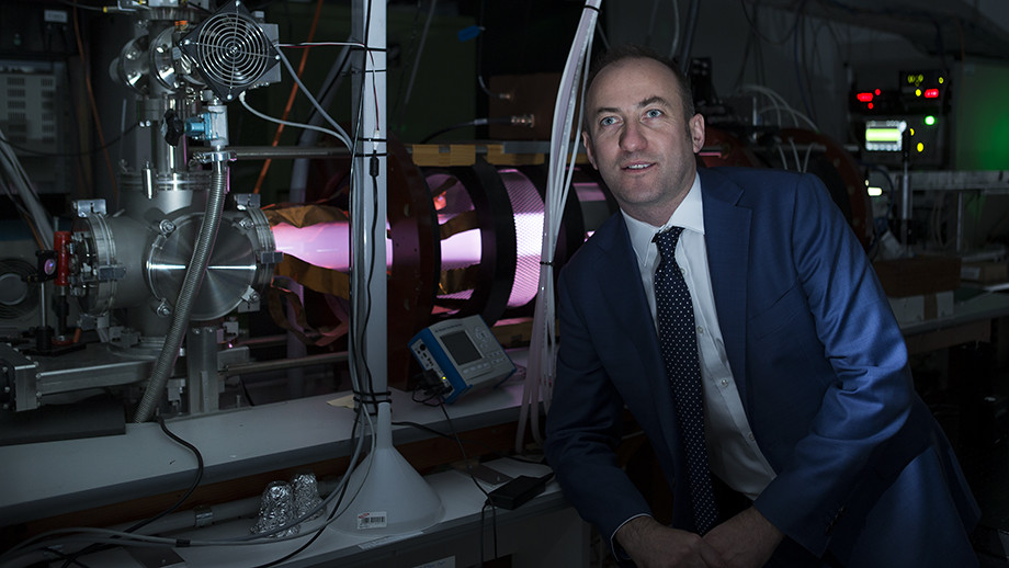 Dr Cormac Corr in front of a high-power linear magnetised plasma machine called MAGPIE I
