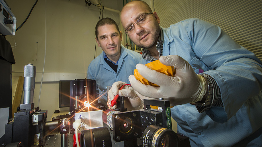 Associate Professor Andrey Miroshnichenko (L) and Dr Mohsen Rahmani demonstrate how the nano material can reflect or transmit light on demand with temperature control. Image: Stuart Hay, ANU