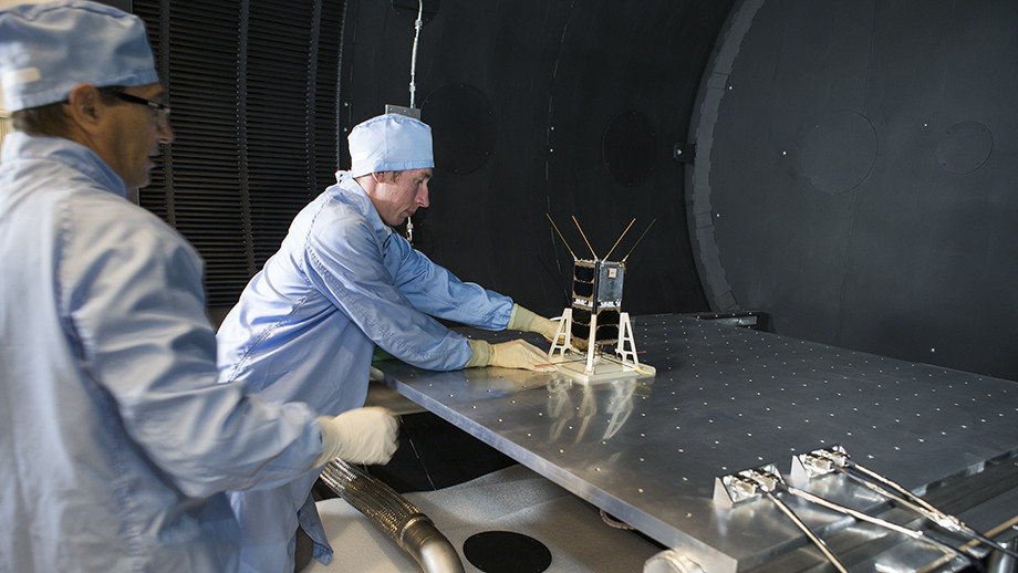 Mike Petrovic (L) and Bart Fordham from ANU load a CubeSat into the space simulator at the ANU Advanced Instrumentation and Technology Centre