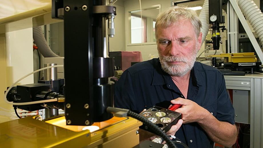 Professor Rainer Grün loads a fossil sample in his lab in RSES. Image Stuart Hay, ANU
