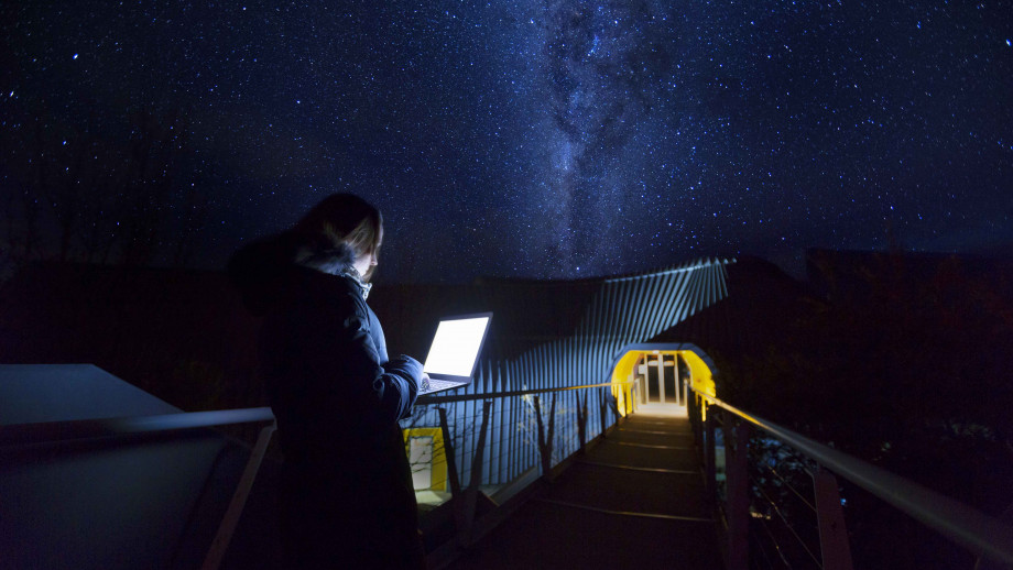 person holding laptop under starry night sky