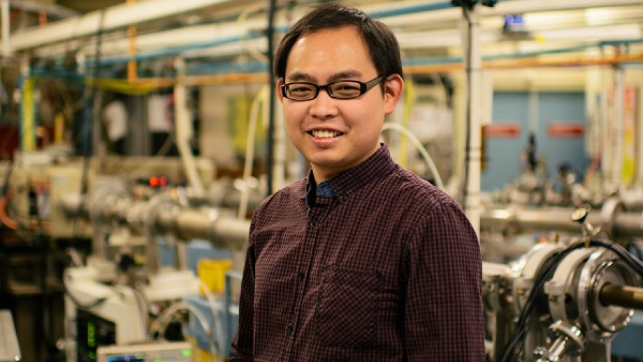 Boon Lee stands smiling in a lab full of machines in the background