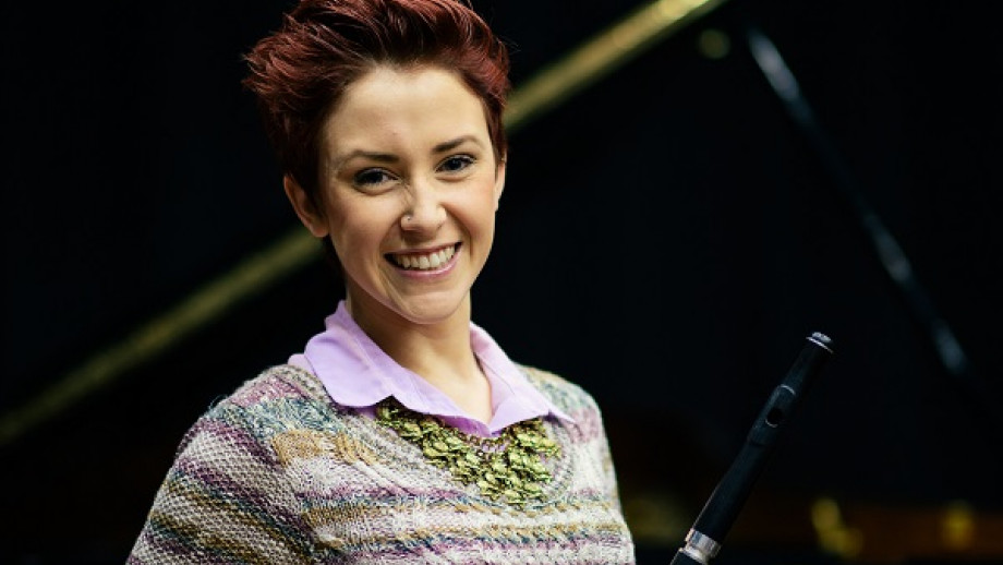 Eliza Shepard stands smiling holding her flute with a black grand piano in the background