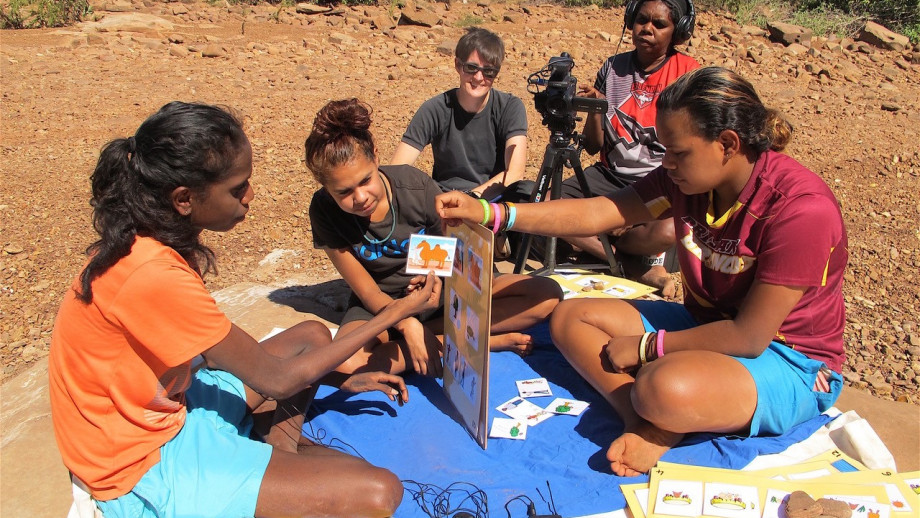 Team members sit with Indigenous community members to collect data.