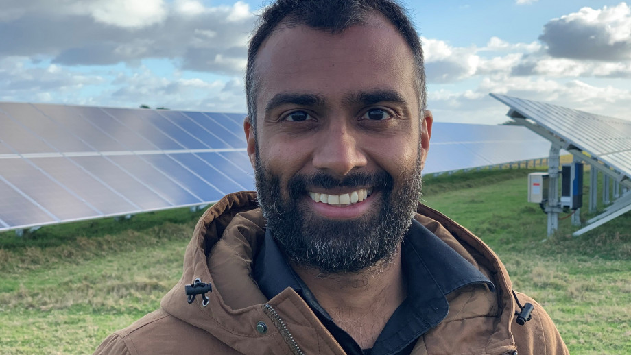 Close-up image of Dr Niraj Lal wearing a brown jacket and smiling. He's standing in front of solar panels.