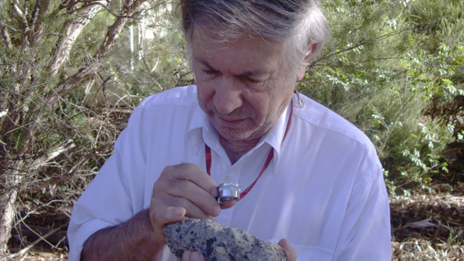 Dr Andrew Glikson with a sample of suveite - a rock with partially melted material formed during an impact. Image: D. Seymour