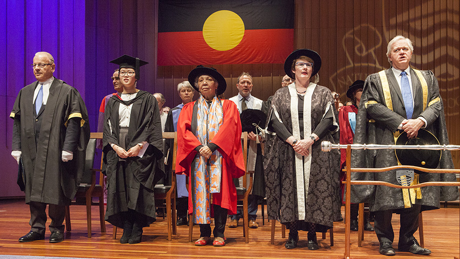 Ngambri-Ngunnawal Elder Matilda House at her honorary conferral, standing alongside members of the ANU executive. Photo by Stuart Hay, ANU.