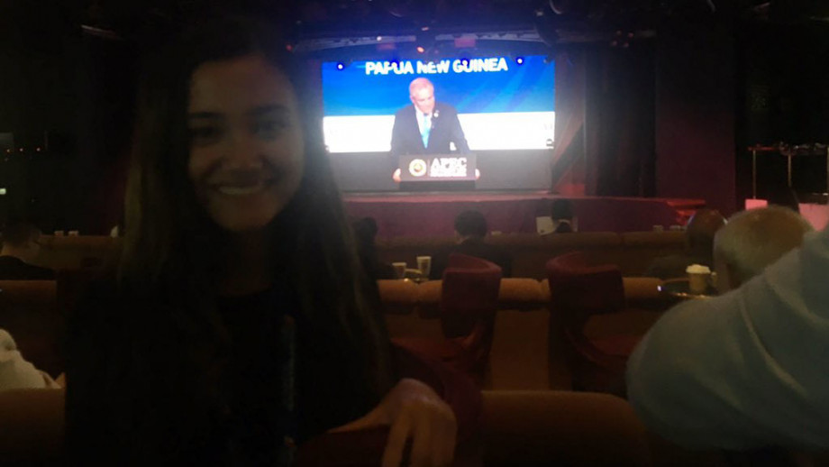 A selfie of Yasmin in front of a screen showing the Prime Minister to Australia, The Hon Scott Morrison, speaking at the Papua New Guinea APEC meeting. Image: supplied.