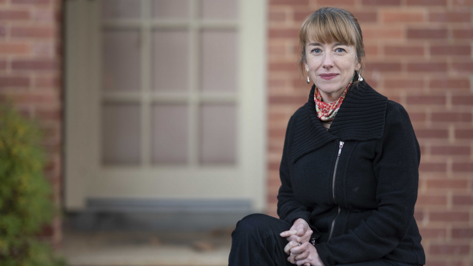 Professor Emily Banks sitting in front of a building