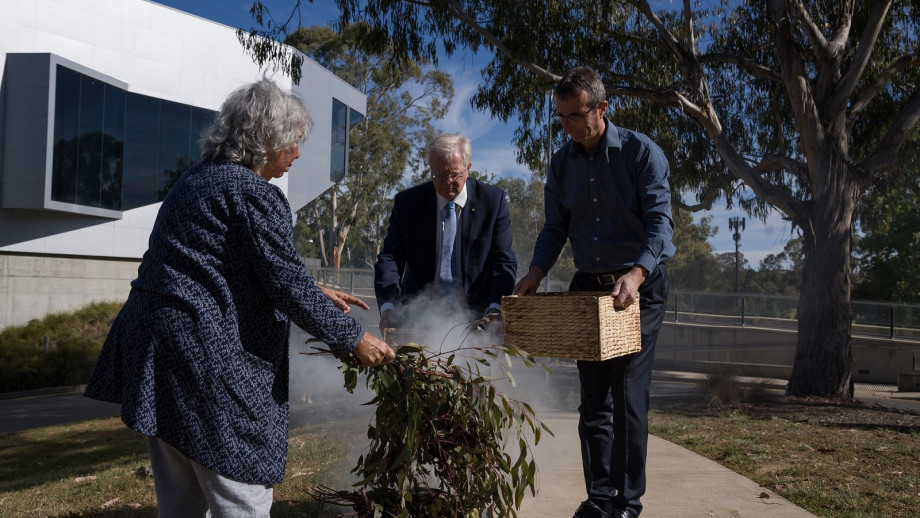 Aunty Maltida House, Professor Brian Schmidt and Professor Graham Mann pass Indigenous blood samples through smoke in a ceremony at ANU. Photo: Lannon Harley