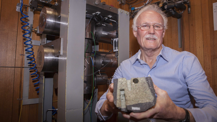 Professor Ian Jackson with a fragment of the Earth's upper mantle, peridotite (green rock inside the black material), brought from around 30km depth within a basaltic magma. Image credit: ANU