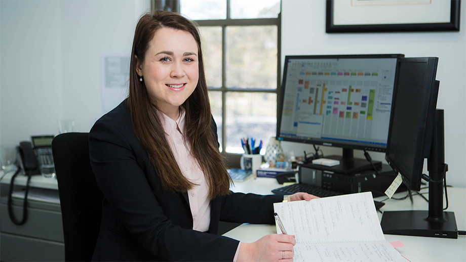 Emily Tighe sitting at her work desk in front of a computer