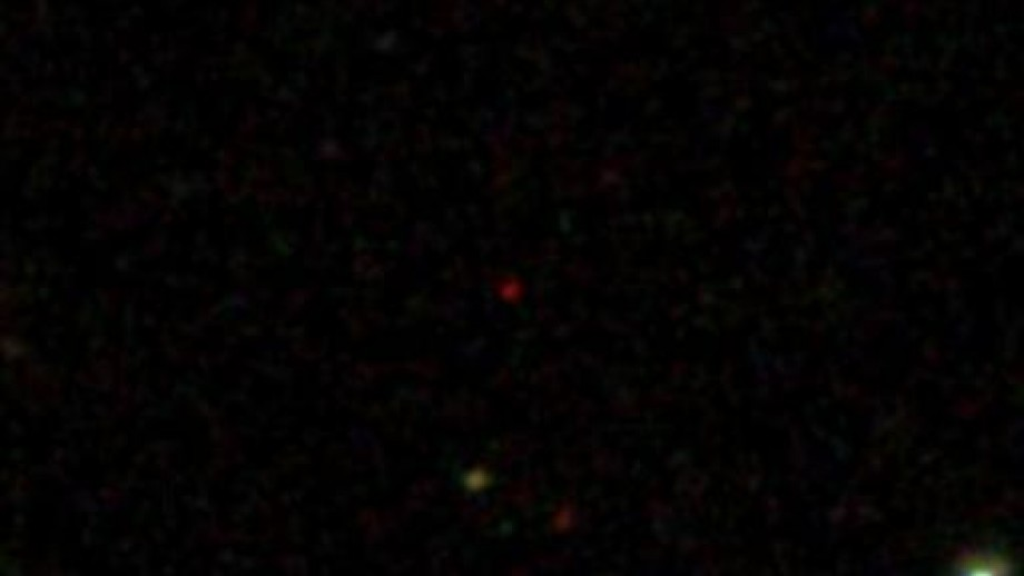 At nearly 13 billion light years distance the ultrabright quasar appears as a tiny red dot in the cente of the image. Credit Sloan Digital Sky Survey
