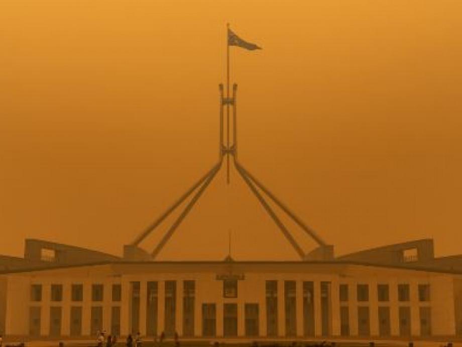 A dense orange haze of bushfire smoke covers Australian Parliament House during the 2019-20 Black Summer Bushfires.