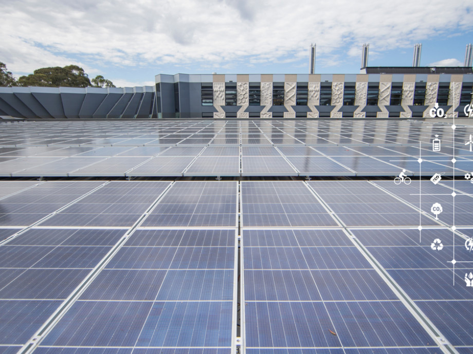 Solar panels on the roof of a building at ANU, with trees in the background and a partly cloudly sky above.