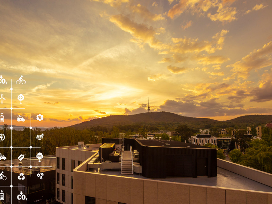 The sun sets behind the Marie Reay building in Kambri, with the silhouette of Telstra Tower and Black Mountain in the background.