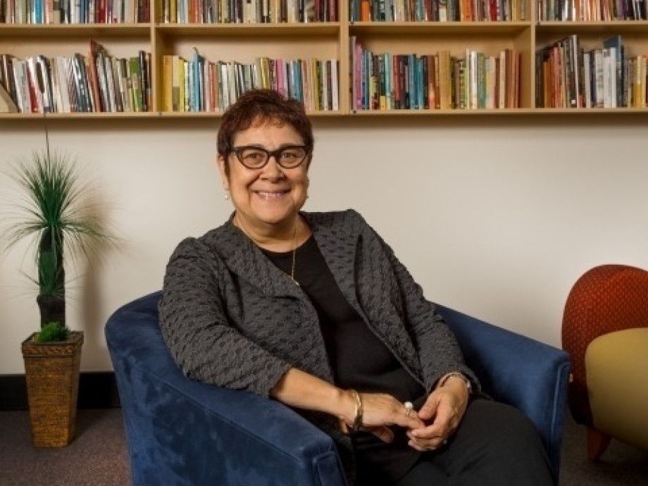 Professor Aileen Moreton-Robinson sits smiling at the camera in front of a row of books.