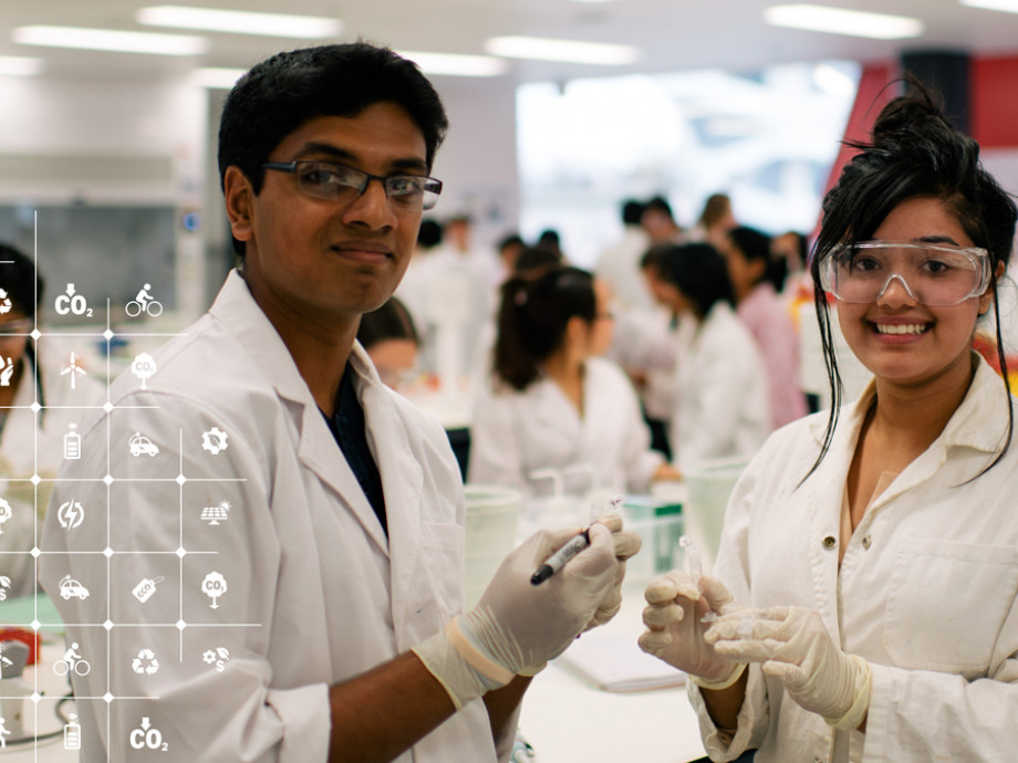 Two students wearing protective glasses and white lab coats smiling at the camera.