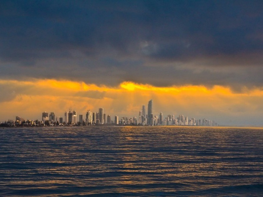 An image of the Gold Coast from the ocean and during a dust storm, with a heavily overcast sky, but rich orangey-golden sunlight streaming through a break in the clouds.